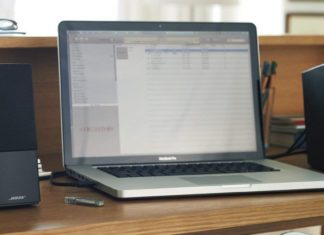 bose speakers next to laptop